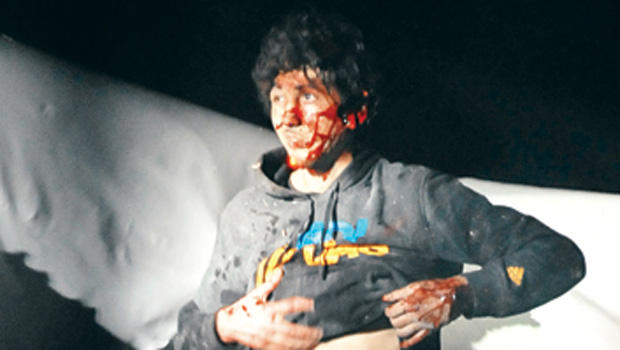 In this photo taken by Sgt. Sean Murphy and published on BostonMagazine.com, Boston bombing suspect Dzhokhar Tsarnaev climbs out of a boat he was hiding in on April 19, 2013. SEAN MURPHY